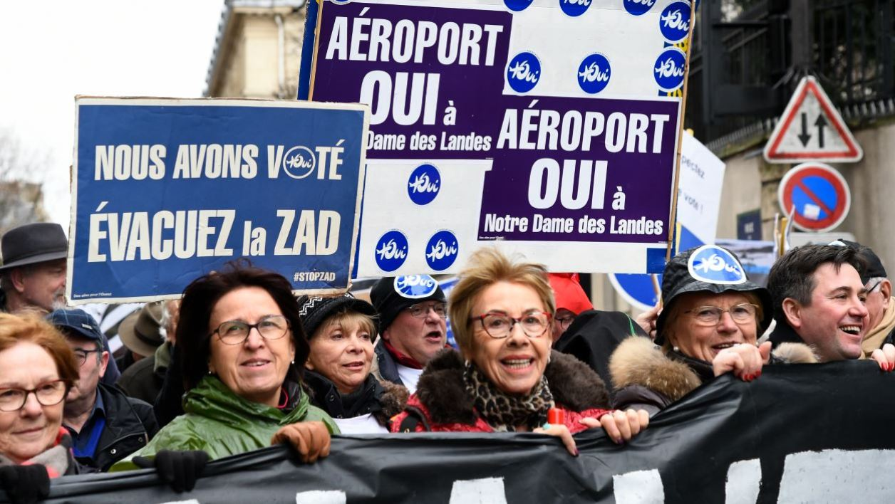 "People hold placards reading ""Yes to the airport"" during a demonstration in support of the controversial Notre-Dame-des-Landes airport project, on December 13, 2017 in Paris.  Bertrand GUAY / AFP"