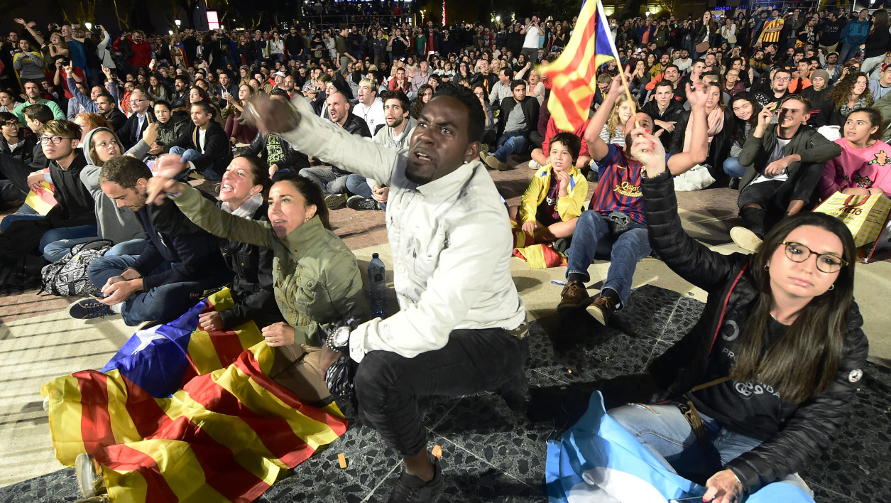 People sit on Plaza Catalunya square in Barcelona waiting for polls results after the closing of polling stations on October 1, 2017.