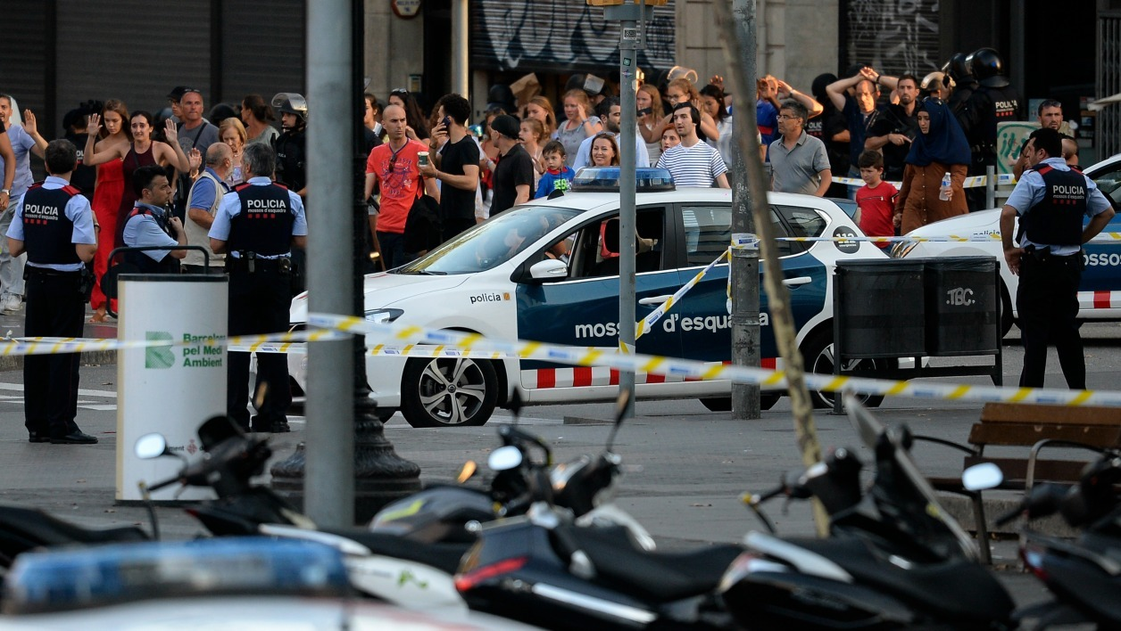 People leave a fastfood with hands up as asked by policemen after a van ploughed into the crowd, killing two persons and injuring several others on the Rambla in Barcelona on August 17, 2017. A driver deliberately rammed a van into a crowd on Barcelona's most popular street on August 17, 2017 killing at least two people before fleeing to a nearby bar, police said.