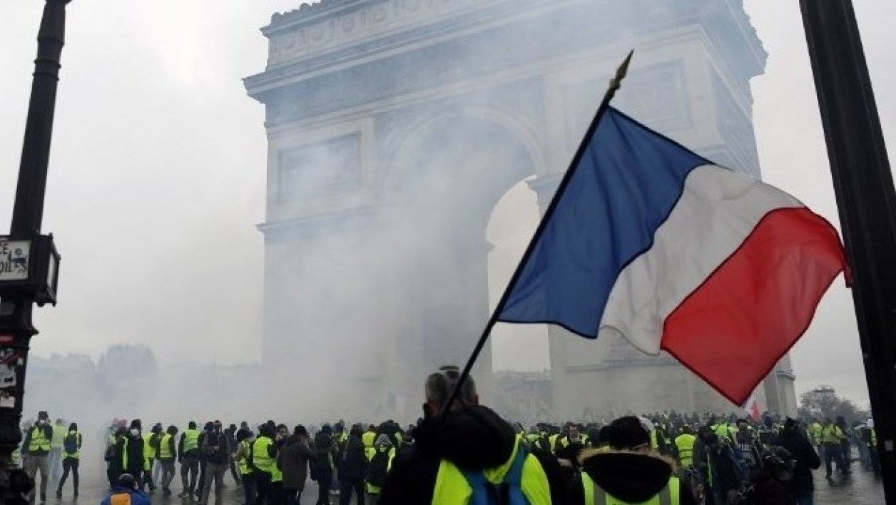 "A demonstrator holds a French flag during a protest of Yellow vests (Gilets jaunes) against rising oil prices and living costs on the Champs Elysees, near the Arc de Triomphe, in Paris, on December 1, 2018. Thousands of anti-government protesters are expected on December 1, 2018 on the Champs-Elysees in Paris, a week after a violent demonstration on the famed avenue was marked by burning barricades and rampant vandalism that French President compared to ""war scenes"". Alain JOCARD / AFP"