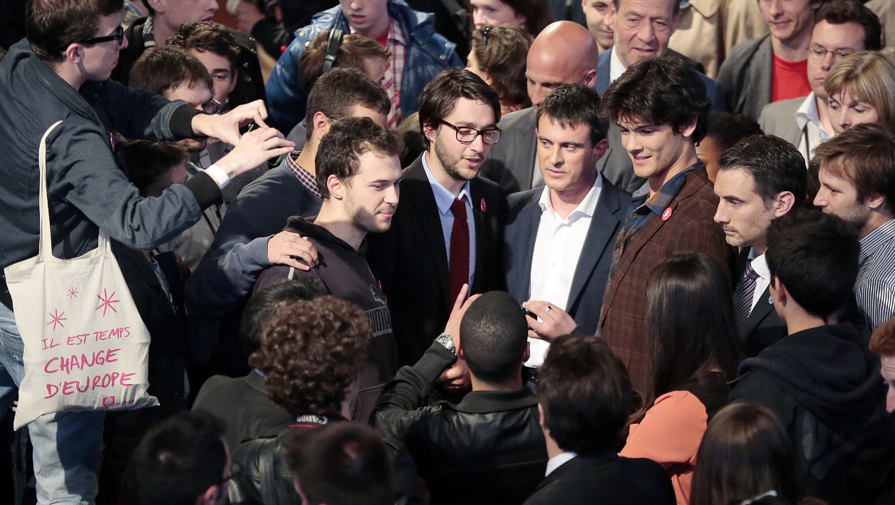 French Prime Minister Manuel Valls (C, with white shirt) is surrounded by supporters after giving the closing speech of a meeting of Young Socialists (MJS) on May 3, 2014 in Nogent sur Marne, outside Paris. AFP PHOTO /JACQUES DEMARTHON JACQUES DEMARTHON / AFP
