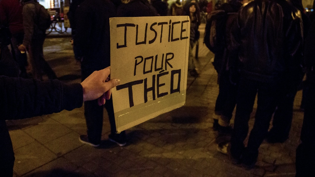 "A demonstrator holds a placard reading ""Justice for Theo"" as people take to the street during a protest in support of a man allegedly abused while in police custody in Aulnay-sous-Bois, on February 9, 2017 in Rennes, northwest France."