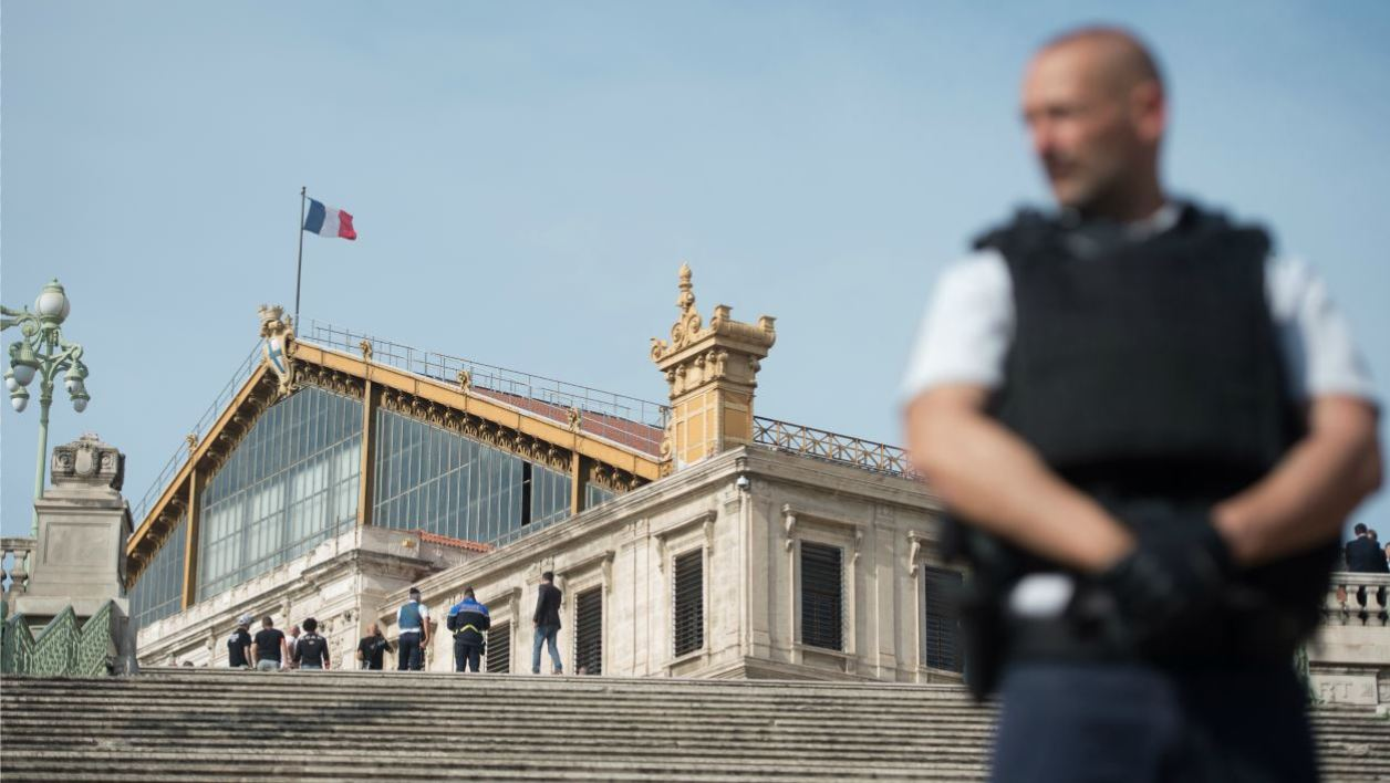 A French police officer stands outside Saint-Charles train station in Marseille on October 1, 2017, after a man armed with a knife killed two people before being shot by soldiers patrolling the area. French anti-terror prosecutors said on October 1 that they had opened an investigation into a knife attack at the main train station in Marseille which left at least two people dead. BERTRAND LANGLOIS / AFP