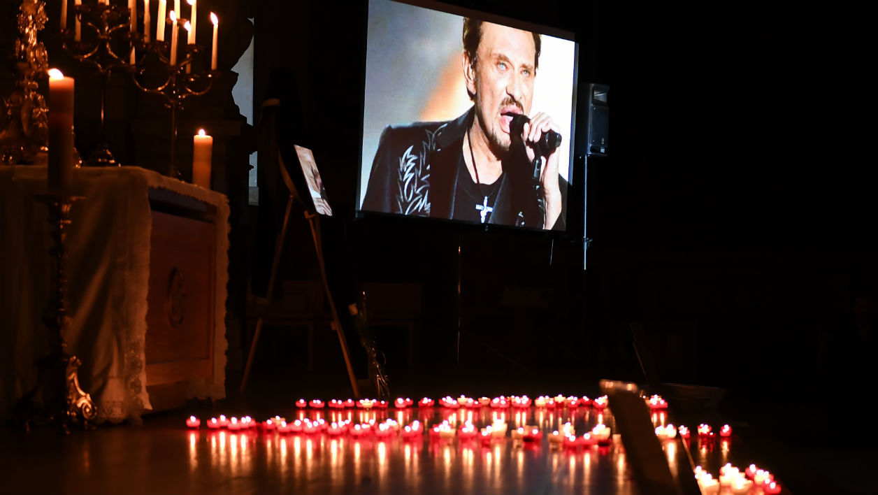 A picture shows layed candles during a prayer vigil in memory of late French rock star Johnny Hallyday at the Saint-Roch Church in Paris on December 7, 2017.