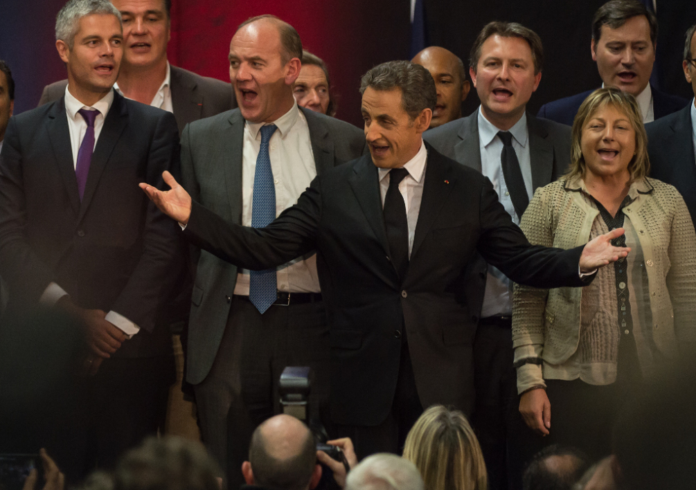 FRANCE, Lambersart : Former French President Nicolas Sarkozy along with party members sings the national anthem during a meeting on September 25, 2014 in the northern city of Lambersart, six days after he announced his political comeback. Sarkozy held his first meeting in Lambersart, hoping again to take over in two months time as chief of his UMP party which is fractured by dissent. A corruption and influence-peddling investigation launched in July against the former French president was suspendedafter he anounced his political comeback. AFP PHOTO PHILIPPE HUGUEN