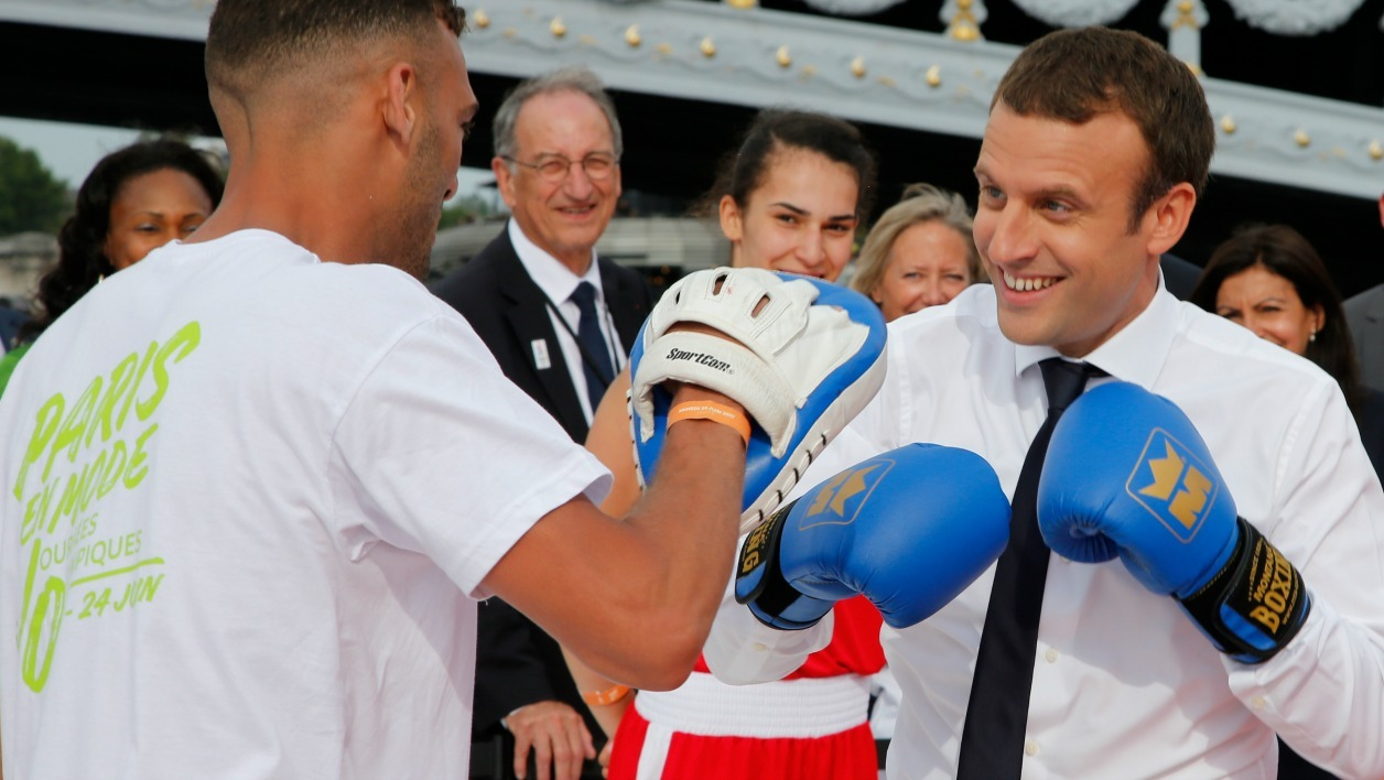 French President Emmanuel Macron (R) spars with a boxing partner on a barge floating on the river Seine in Paris on June 24, 2017 in a bid to promote the candidacy of the city of Paris for the Summer Olympics Games in 2024.  JEAN-PAUL PELISSIER / POOL / AFP