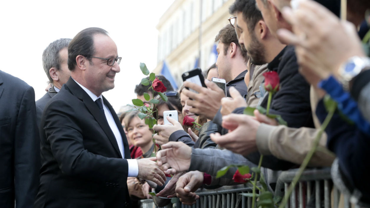 French outgoing President Francois Hollande (L) greets supporters as he arrives at the Socialist Party's (PS) heaquarters on May 14, 2017 in Paris following the handover and inauguration ceremonies of his succesor.  Joël SAGET / AFP