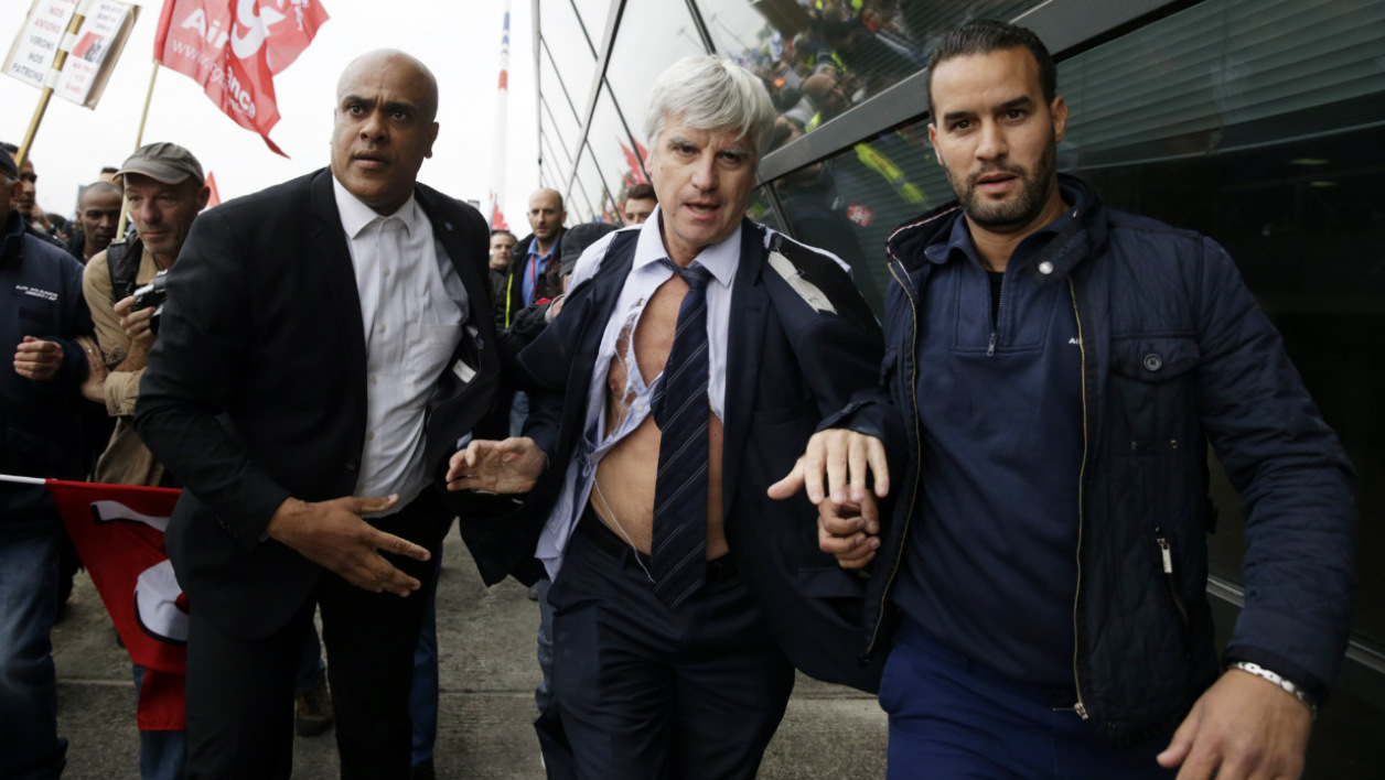 chemise arrachée déchirée - Director in charge of human resources of Air France long-haul flights, Pierre Plissonnier (C), nearly shirtless, runs away from the demonstrators, helped by security officers, after several hundred employees stormed into the offices of Air France, interrupting the meeting of the Central Committee (CCE) in Roissy-en-France, on October 5, 2015. Air France-KLM unveiled a revamped restructuring plan on October 5 that could lead to 2,900 job losses after pilots for the struggling airline refused to accept a proposal to work longer hours. AFP PHOTO / KENZO TRIBOUILLARD  KENZO TRIBOUILLARD / AFP
