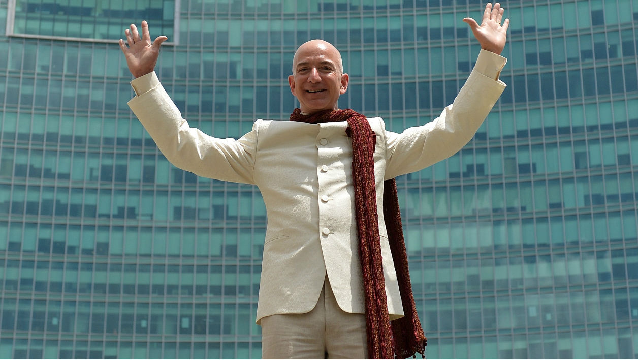 US founder and CEO of Amazon.com Jeff Bezos poses atop a lorry after handing over a two billion dollar cheque to Indian Vice President and Country Manager of Amazon.in, Amit Agarwal (unseen) in Bangalore on September 28, 2014. The investment will go towards raising the bar for online shopping in India