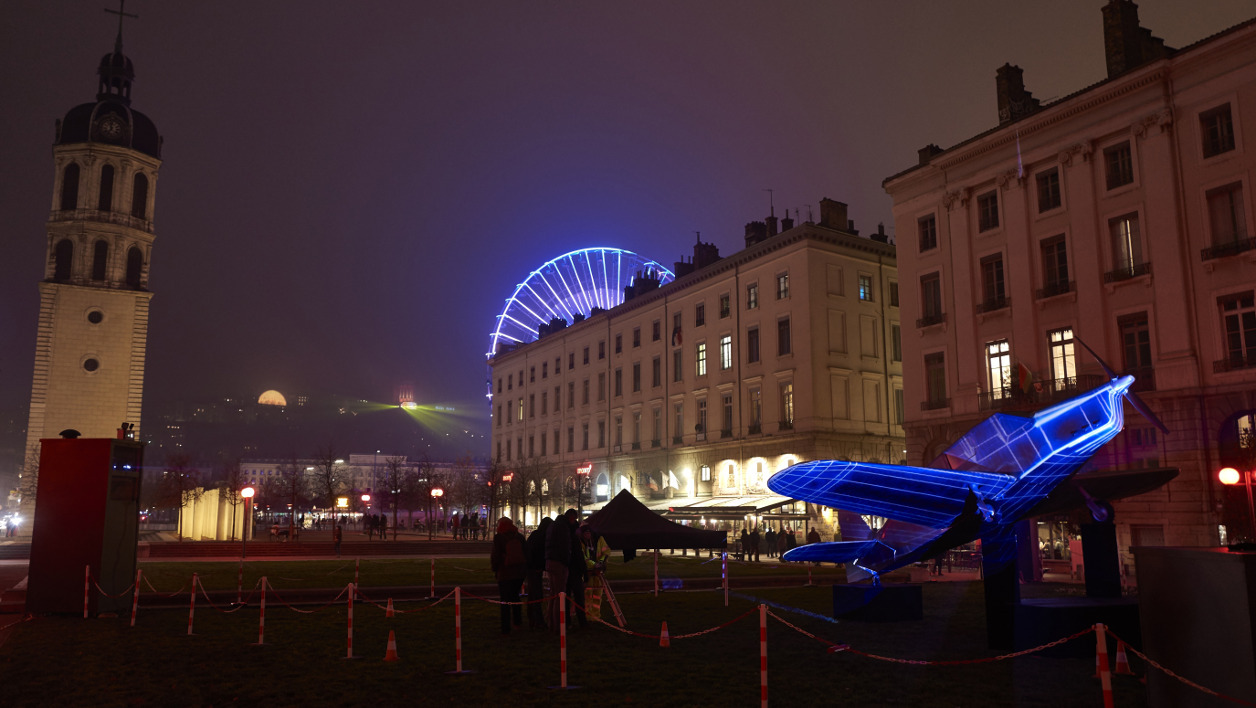 "The Ferris wheel of Place Bellecour (Rear), the bell tower (L) and an illuminated plane sculpture inspired by ""Vol de Nuit"" (Night Flight, Antoine de Saint-Exupery's 1931 novel) are pictured in downtown Lyon on December 7, 2016 during rehearsals on the eve of the 18th edition of the Festival of Lights (Fete des Lumieres), which marks each year since December 8, 1852 on the feast of Immaculate Conception a tribute to Mary, mother of Jesus, after the town was spared by the 1643 plague.  JEAN-PHILIPPE KSIAZEK / AFP"