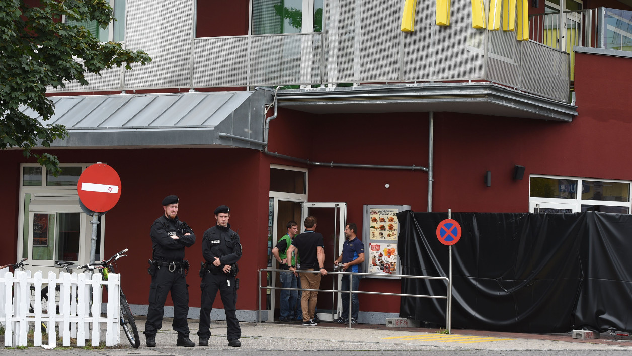 Policemen stand in front of a fast food restaurant near the Olympia-Einkaufszentrum shopping centre on July 23, 2016, one day after the attack at the shopping centre in the Bavarian capital. Police were probing the motives of the lone teenage German-Iranian gunman who went on a deadly rampage at a busy Munich shopping centre, the third bloody attack on civilians in Europe in just over a week. Nine people were killed and another 16 wounded as the black-clad gunman brought terror to Germany's third largest city on Friday evening, July 22, 2016, before committing suicide. Christof Stache / AFP