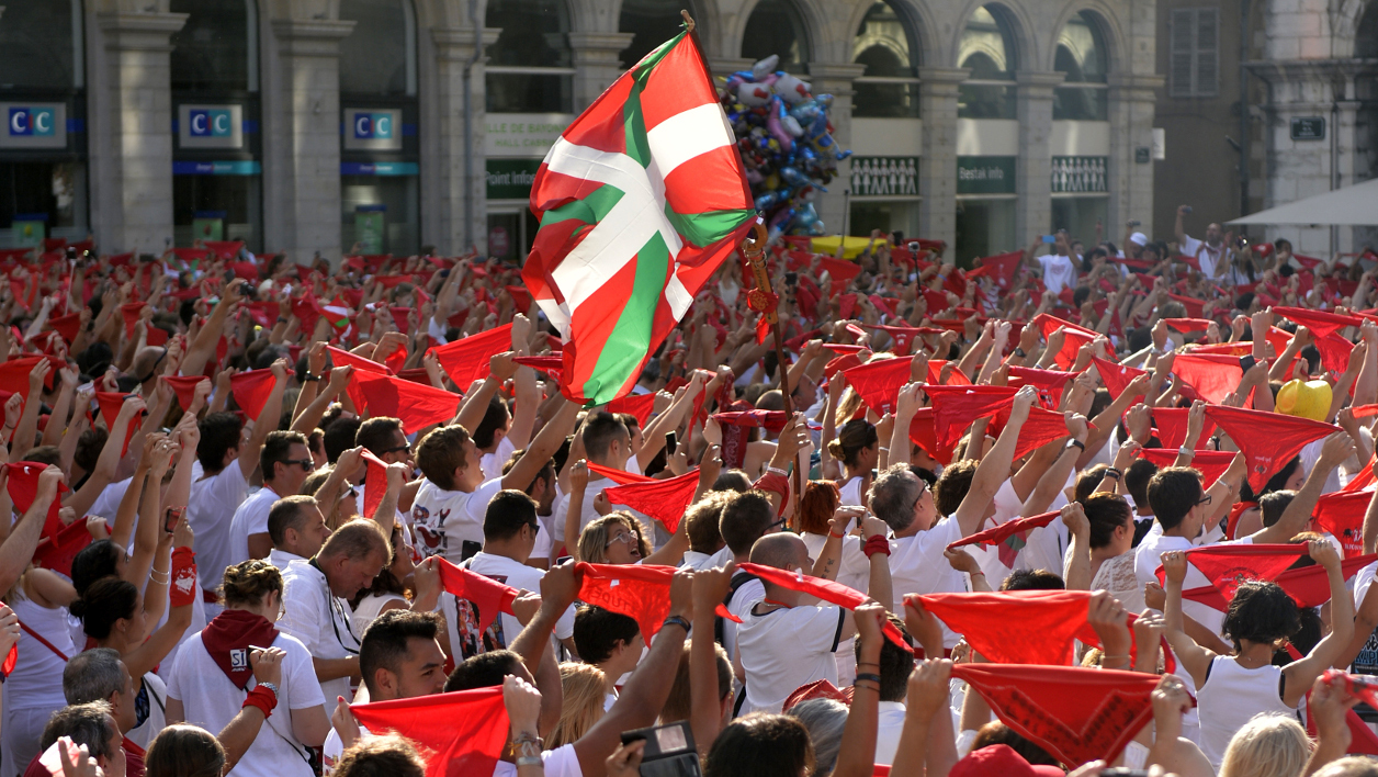 People cheer as they wave bandanas in Bayonne, southwestern France on July 27, 2016, during the typically Basque Bayonne festival (Fetes de Bayonne). The 80th Bayonne festival (Fetes de Bayonne), one of the largest popular event in the world, starts on July 27, 2016 with enhanced security measures, two weeks after the Nice attack in Nice. GAIZKA IROZ / AFP