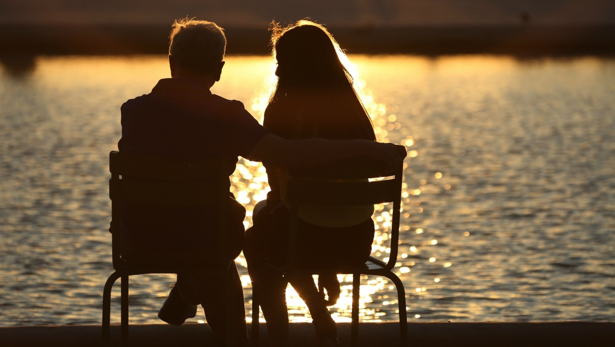 A couple enjoys sunset on July 11, 2015 in the Tuileries gardens in Paris. AFP PHOTO / LUDOVIC MARIN  LUDOVIC MARIN / AFP