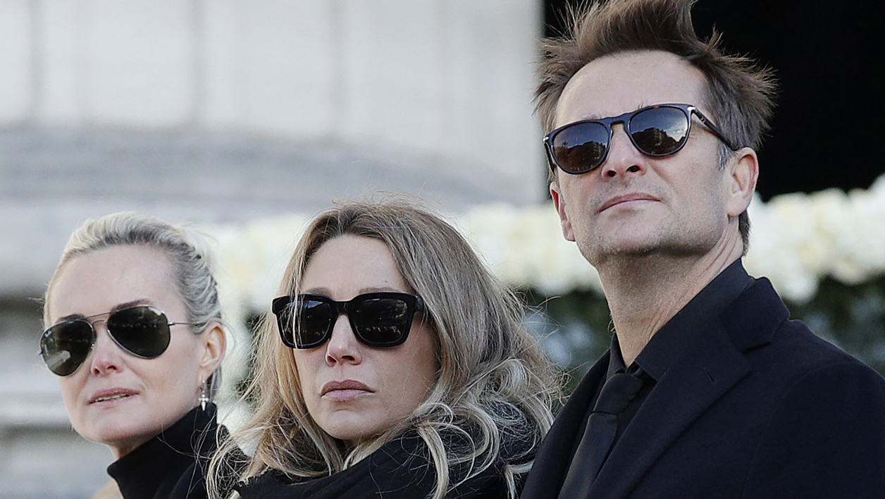 In this file photo taken on December 09, 2017 Laeticia Hallyday, (L), wife of late French singer Johnny Hallyday, David Hallyday, son of Johnny Hallyday and daughter Laura Smet (C) stand during the funeral ceremony for Johnny Hallyday outside the Eglise de la Madeleine (La Madeleine Church) in Paris, on December 9, 2017.