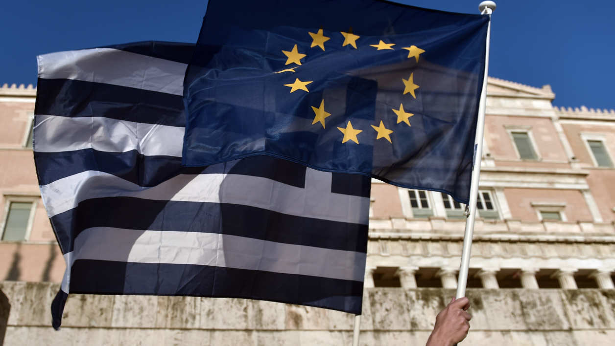 drapeau européen UE zone euro drapeau Grèce A protester waves an EU and a Greek flag during a pro-European demonstration in front of the Greek parliament in Athens on June 18, 2015. Greece must make the next move towards reaching a debt deal with its EU-IMF creditors but there is little chance of an agreement at a meeting of eurozone finance ministers on June 18, Eurogroup chief Jeroen Dijsselbloem said. AFP PHOTO / ARIS MESSINIS