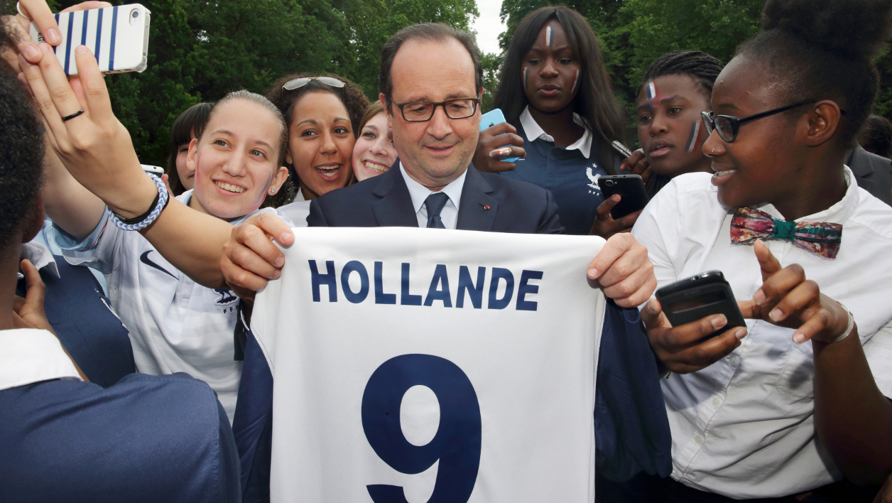 French President Francois Hollande (C) holds a jersey as he poses with players pf women's football teams Paris FC and Cosmos Taverny, during a break in the 2014 World Cup match between France against Nigeria, at the Elysee presidential palace in Paris, on June 30, 2014. AFP PHOTO / POOL / PHILIPPE WOJAZER