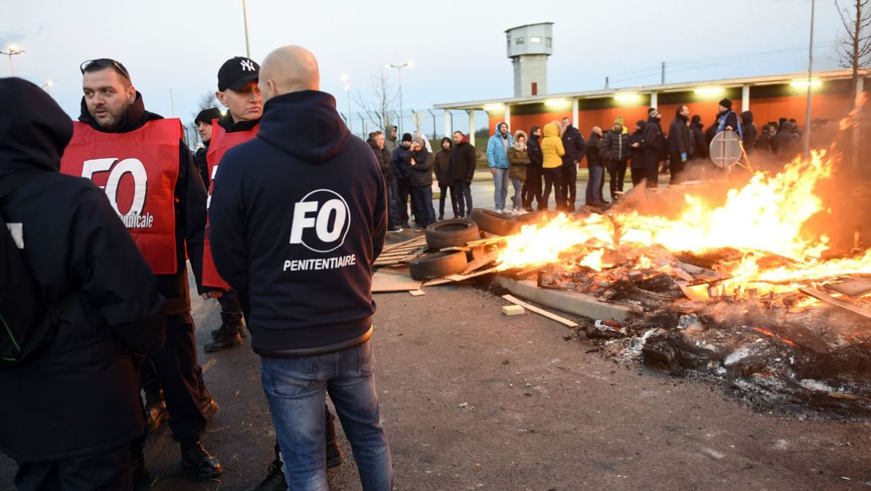 Prison guards stand next to burning wooden palettes as they block access to Vendin-le-Vieil prison on January 16, 2018 to demand tighter security after three officers were injured in an attack by a German terror convict last week. French prison officers blocked access to several jails around the country on January 15.
