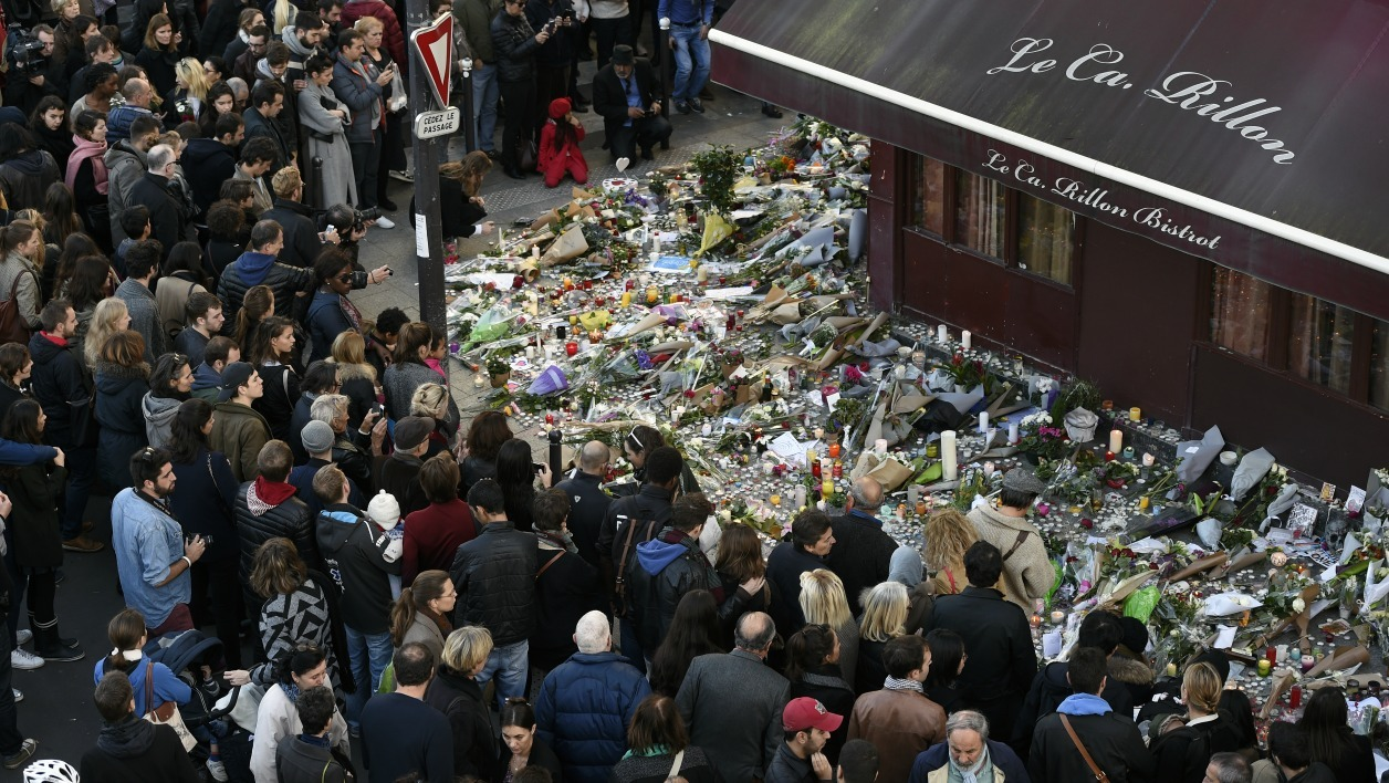"People gather at a makeshift memorial in front of ""Le carillon"" restaurant on November 15, 2015, in the 10th district of Paris, following a series of coordinated terrorists attacks on November 13. Islamic State jihadists claimed a series of coordinated attacks by gunmen and suicide bombers in Paris that killed at least 129 people in scenes of carnage at a concert hall, restaurants and the national stadium. AFP PHOTO / ALAIN JOCARD"