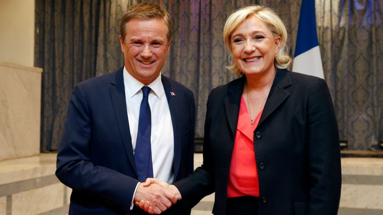 Former French presidential election candidate for the right-wing Debout la France (DLF) party Nicolas Dupont-Aignan (L) and French presidential election candidate for the far-right Front National (FN) party Marine Le Pen, shake hands at the end of a joint statement at FN headquarters in Paris, on April 29, 2017.