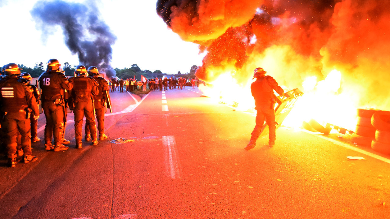 Riot police prepare to intervene to disperse refinery worker holding a blockade of the oil depot of Douchy-Les-Mines to protest against the government's proposed labour reforms, on May 25, 2016. Refinery workers stepped up strikes that threaten to paralyse France weeks ahead of the Euro 2016 tournament as the government moved to break their blockades, escalating a three-month tug-of-war over labour reforms. FRANCOIS LO PRESTI / AFP