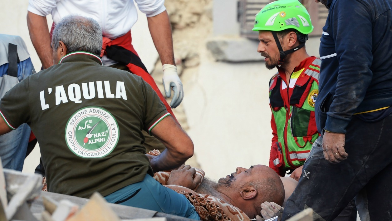 Rescuers help an injured man on August 24, 2016 in Amatrice after a powerful earthquake rocked central Italy. A powerful pre-dawn earthquake devastated mountain villages in central Italy, leaving at least 73 people dead, dozens more injured or trapped under the rubble and thousands temporarily homeless.