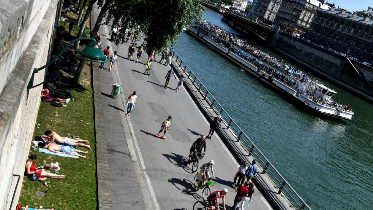 People enjoy a sunny day on the Seine river bank in Paris on May 6, 2018.  GERARD JULIEN / AFP