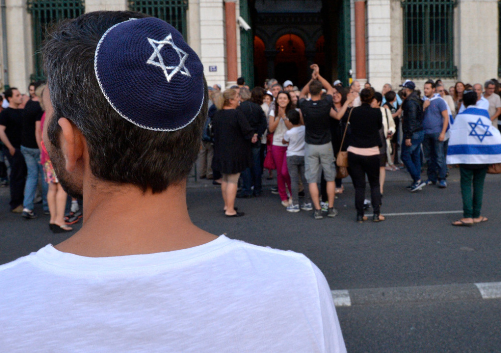 FRANCE, Lyon : A man wearing a skullcap looks on as people take part in a demonstration called by the Representative Council of Jewish Institutions in France (CRIF) on July 31, 2014 in front of Lyon's synagogue, as France is considering disbanding a radical Jewish group, the Jewish Defence League (LDJ), whose members clashed with pro-Palestinian activists during rallies over Israel's offensive in Gaza. The rally is in response to weeks of pro-Palestinian protests marred by clashes, arrests and allegations of anti-Semitism in which synagogues were targeted and Israeli flags burnt. AFP PHOTO / ROMAIN LAFABREGUE