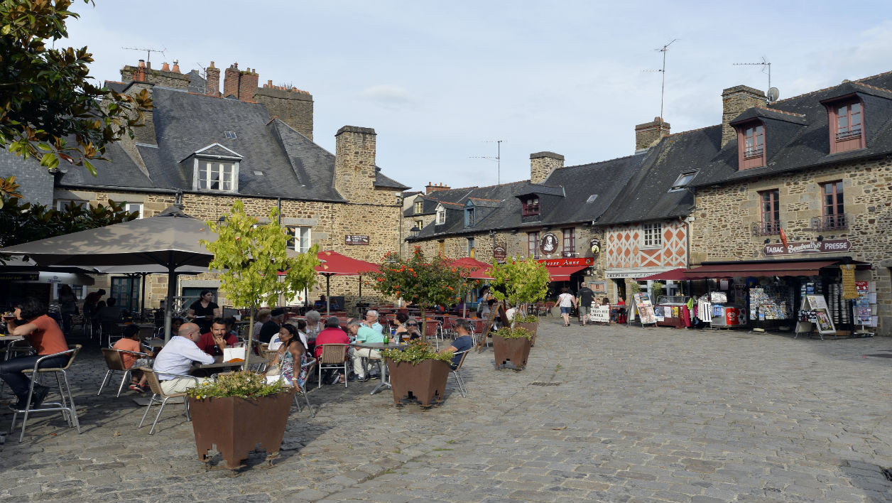 People sit at a restaurant's terrace on a square near the fortified castle of Fougeres, western France. The medieval city of Fougeres traces its origins back to the end of the Xth century. AFP PHOTO / MIGUEL MEDINA MIGUEL MEDINA / AFP