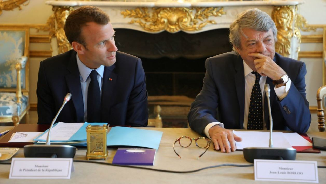 French president Emmanuel Macron (L), flanked by former Environment minister Jean-Louis Borloo, in charge of a mission on the priority neighbourhoods in the French urban policy, attends the presentation of a battle plan for the country's most deprived areas, on May 22, 2018 in Paris.  ludovic MARIN / POOL / AFP