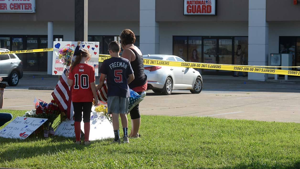 CHATTANOOGA, TN - JULY 16: Zach, Zoe and Melissa Cates add to a makeshift memorial near the scene of a shooting at a Armed Forces Career Center/National Guard recruitment office on July 16, 2015 in Chattanooga, Tennessee. According to reports, Mohammod Youssuf Abdulazeez, 24, opened fire on a military recruiting station at a strip mall and then killed four U.S. Marines at an operational support center operated by the U.S. Navy at another location more than seven miles away, where the gunmen himself was also killed. Jason Davis/Getty Images/AFP
