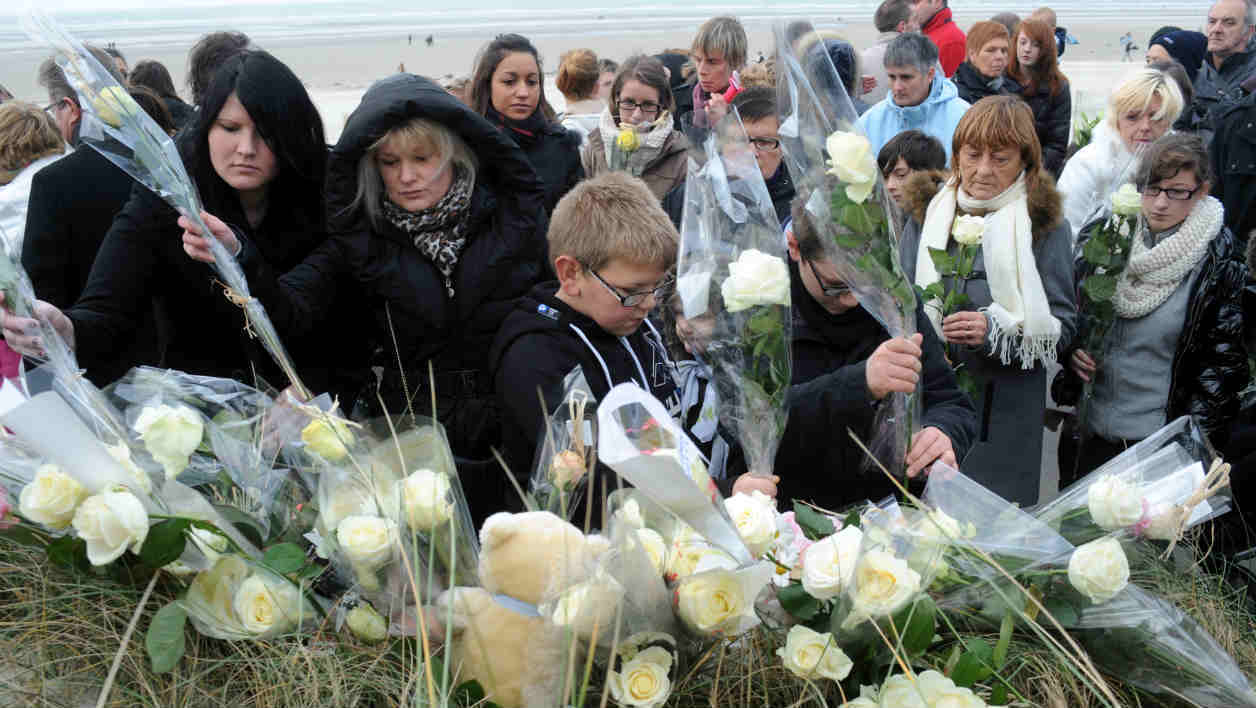 "Inhabitants of Berck-sur-Mer, Northern France lay bouquets of flowers as they take part on November 30, 2013 to a ""white march"" in homage to the girl found dead on the beach on November 20, 2013. A 36 year-old woman arrested on November 29, 2013 in Saint-Mande, outside Paris, confirmed having killed her daughter and is presented to the judge on November 30, 2013 at the Courthouse in Boulogne-sur-Mer, Northern France. AFP PHOTO / FRANCOIS LO PRESTI"