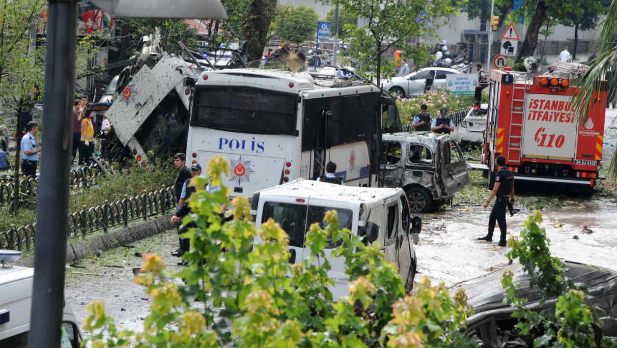 Police officers and rescuers inspect the site of a bomb attack that targeted a police bus in the Vezneciler district of Istanbul on June 7, 2016. A bomb attack targeted Turkish police in a central Istanbul district on June 7, 2016, leaving several people wounded, the state-run TRT television reported. STRINGER / DOGAN NEWS AGENCY / AFP