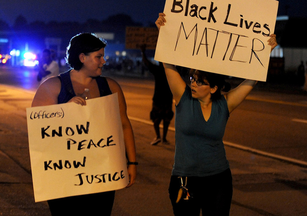 UNITED STATES, FERGUSON : Demonstrators display signs during a protest on West Florissant Avenue in Ferguson, Missouri on August 18, 2014. Police fired tear gas in another night of unrest in a Missouri town where a white police officer shot and killed an unarmed black teenager, just hours after President Barack Obama called for calm. AFP PHOTO / Michael B. Thomas