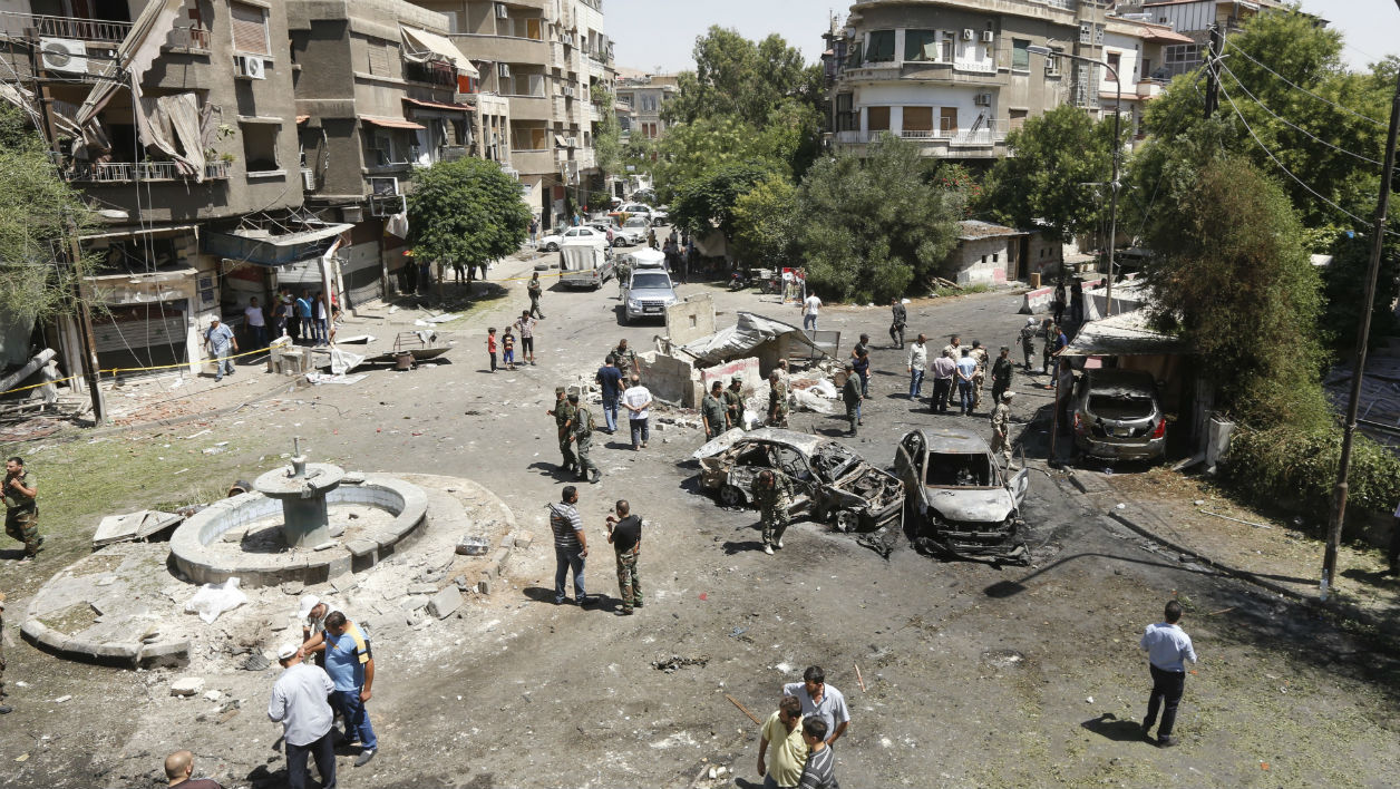Syrians gather to inspect the damage at the site of a suicide bomb attack in the capital Damascus' eastern Tahrir Square district, on July 2, 2017. LOUAI BESHARA / AFP