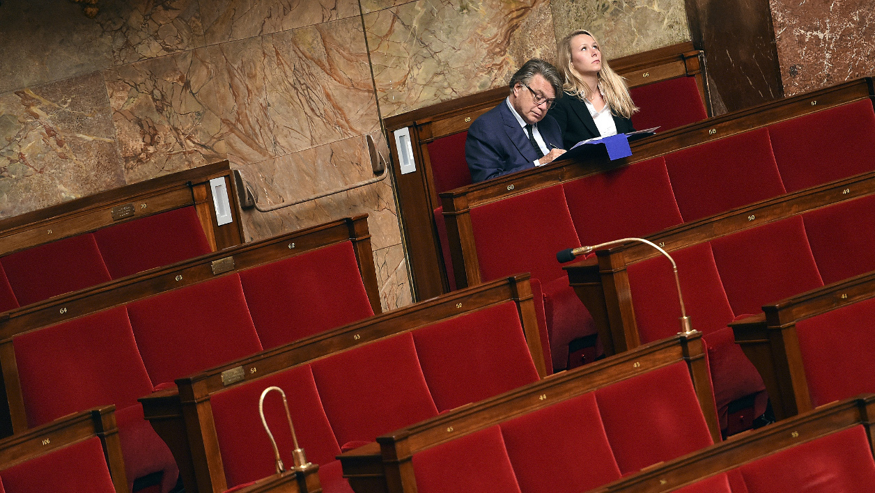 French MPs Marion Marechal Le Pen (R) and Gilbert Collard of the far-right National Front (FN) attend a parliament session to a vote on a surveillance bill at the National Assembly in Paris on June 24, 2015. The French parliament adopted a controversial bill aimed at broadening eavesdropping as part of efforts to counter terrorism. AFP PHOTO / LOIC VENANCE  LOIC VENANCE / AFP