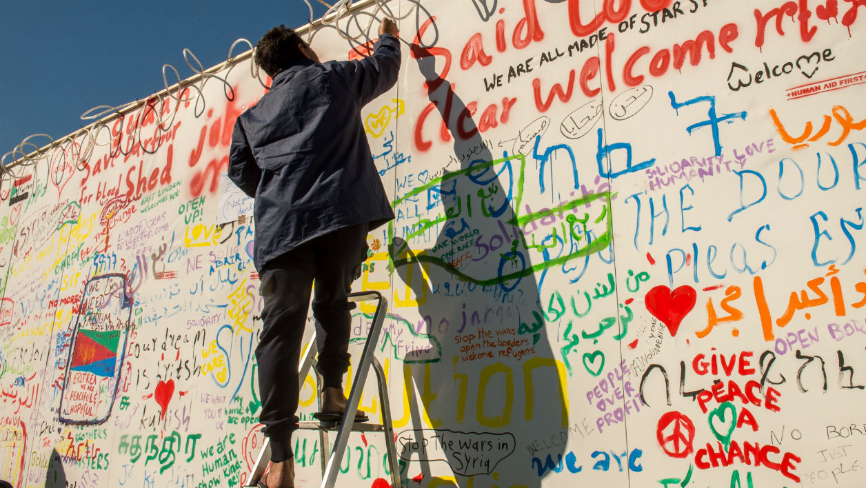 Un migrant inscrit un message sur un mur du terminal de ferry de Calais (photo d'illustration)
