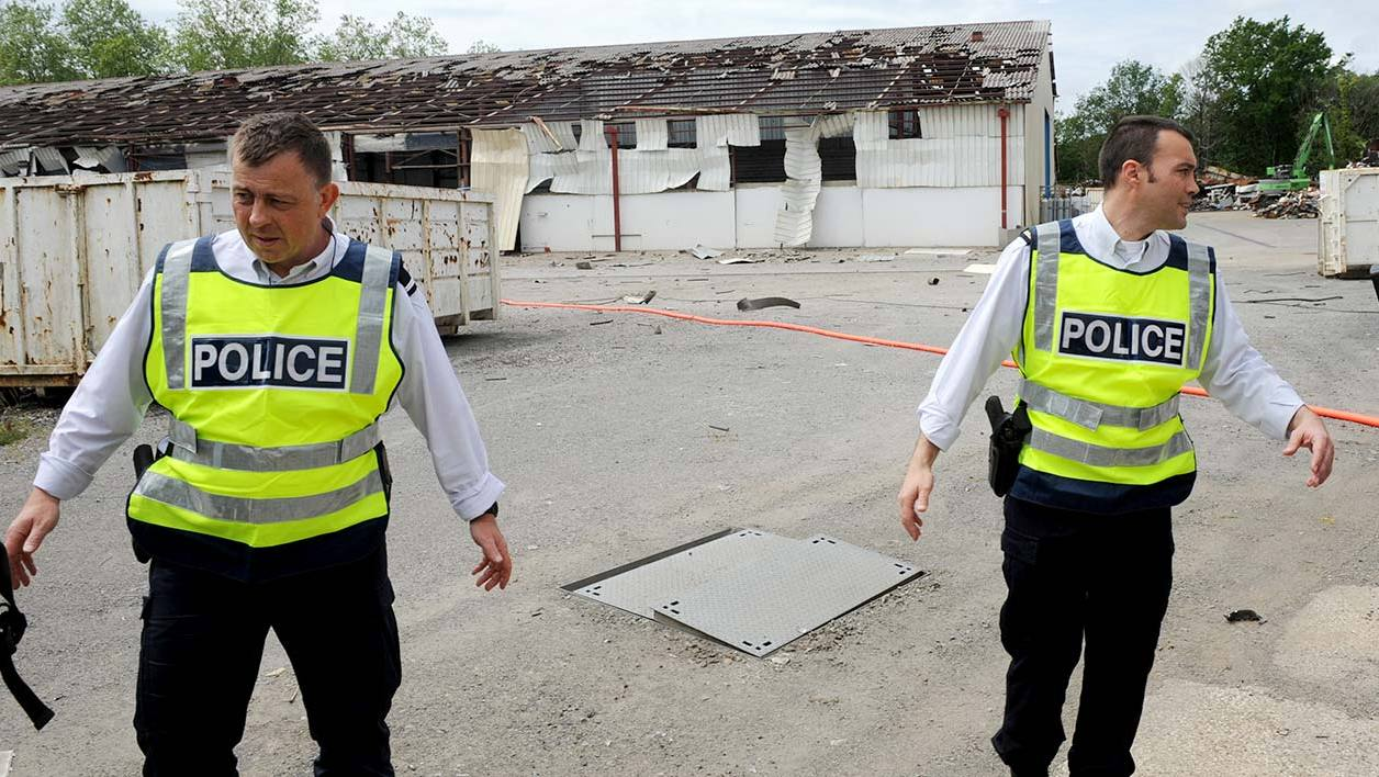 Policemen walk in front of the hangar where an explosion allegedly due to acetylene gas killed two people and wounded three at the Derichebourg factory in the northern Bayonne industrial zone, on May 12, 2016.  IROZ GAIZKA / AFP