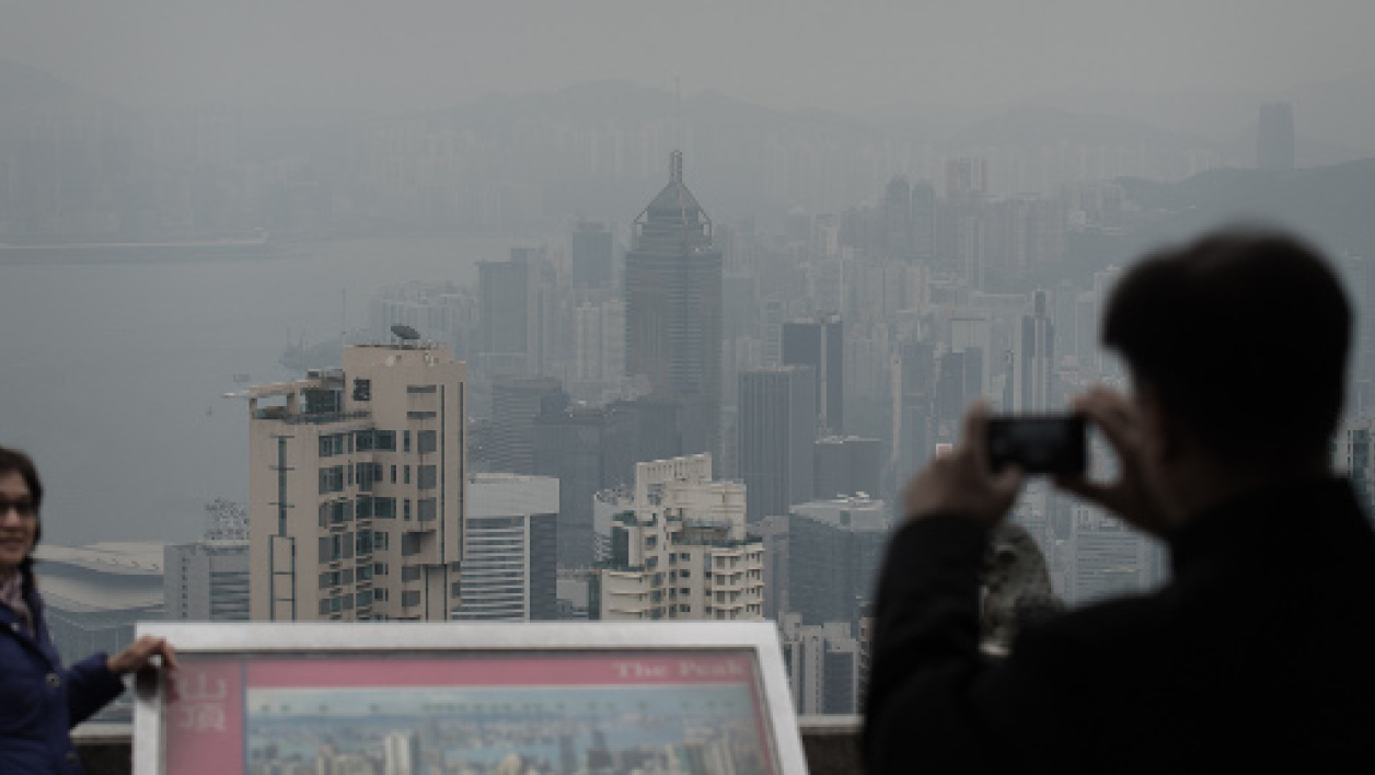 Des touristes immortalisent le nuage de pollution permanent qui flotte au-dessus de Hong Kong.
