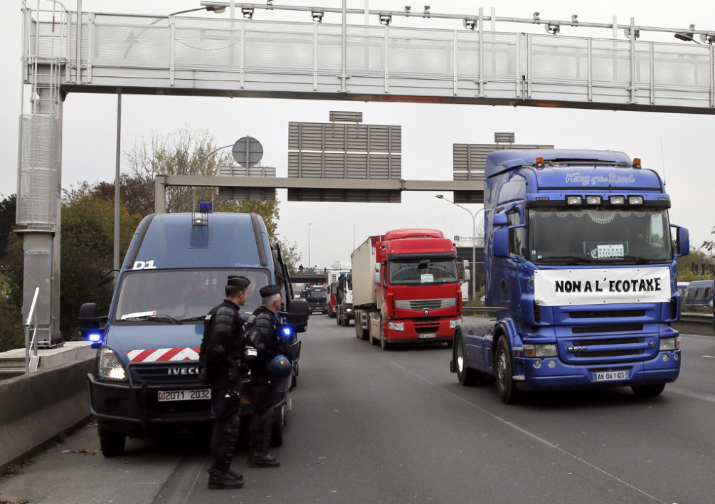 """Trucks drive under the Rungis highway bridge with radars set up to collect the environmental tax """"Ecotaxe"""", on November 16, 2013 near Rungis, as part of a protest against an environmental tax. Protests over the new """"ecotax"""" on trucks, which aims to encourage environmentally friendly commercial transport, kicked off in earnest last month in the northwestern region of Brittany and eventually forced the government to backtrack and suspend the levy. On the truck, a banner reads """"No to ecotax"""". AFP PHOTO / PATRICK KOVARIK"""