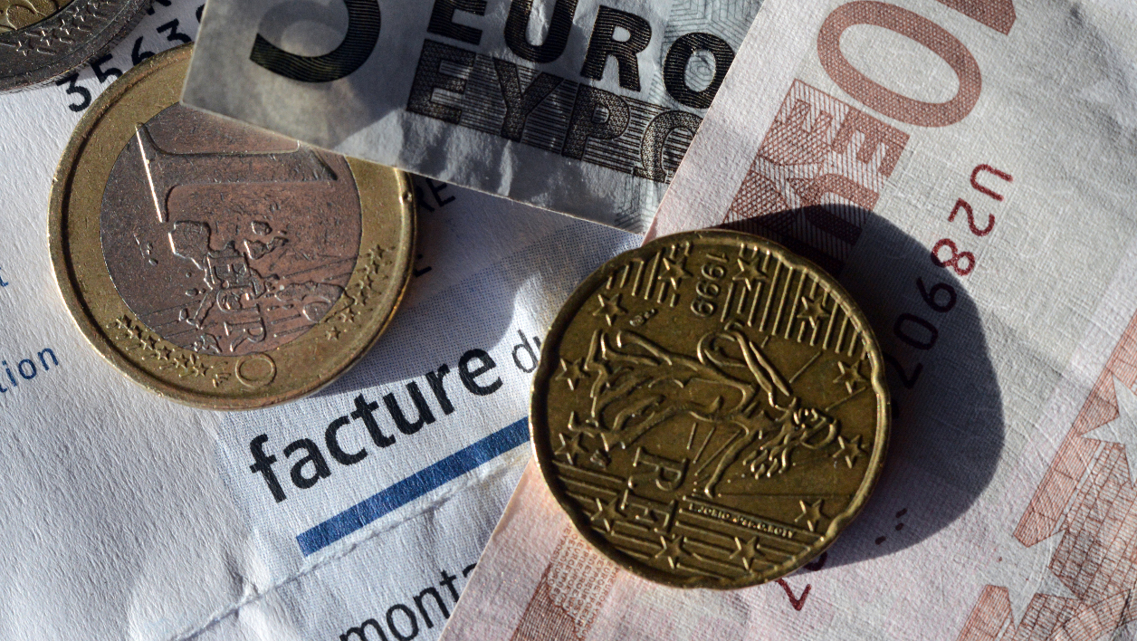 Argent, pièces, billets - This picture taken on January 01, 2013 shows a EDF electricity bill with euros coins on in the western city of Rennes. AFP PHOTO / DAMIEN MEYER DAMIEN MEYER / AFP