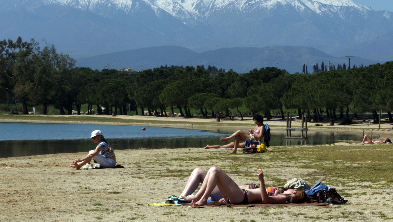 People enjoy the sunny spring weather at the Villeneuve-de-la-Raho lake near Perpignan, southern France on April 8, 2011 with the mount Canigou, part of French Pyrenees mountains, in the background. AFP PHOTO / RAYMOND ROIG RAYMOND ROIG / AFP