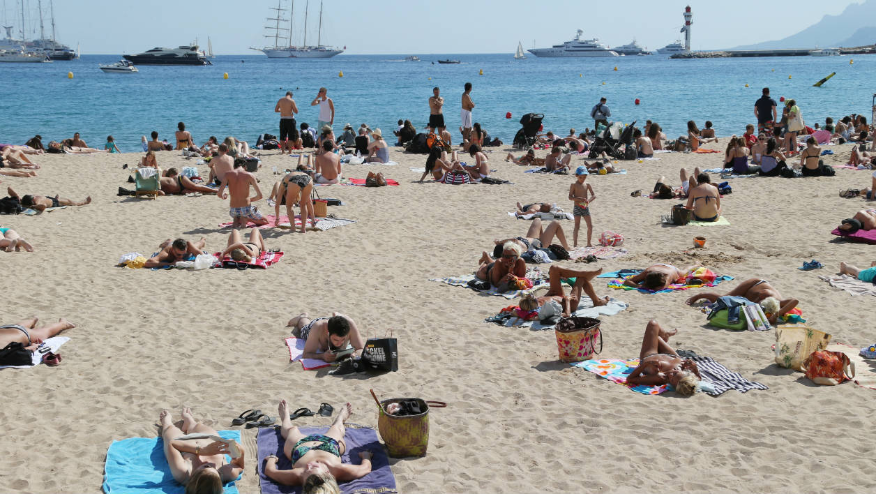 People sunbath on the beach during the 67th edition of the Cannes Film Festival in Cannes, southern France, on May 17, 2014. AFP PHOTO / LOIC VENANCE