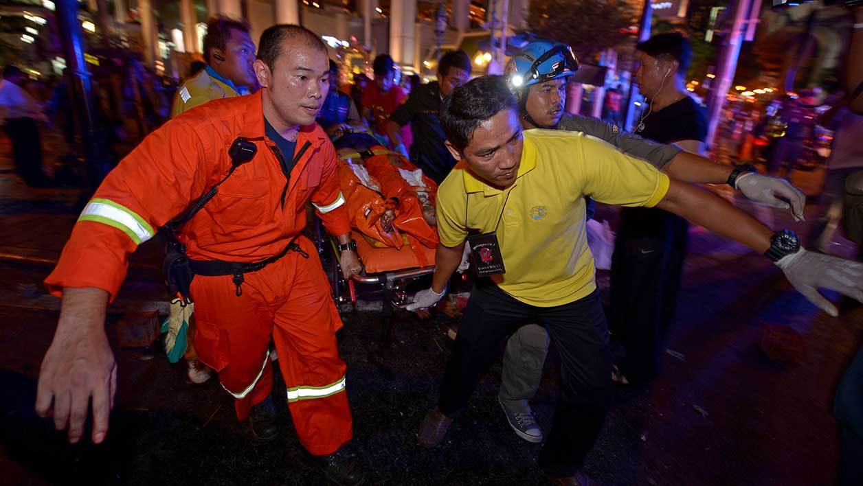 Thai rescue workers carry an injured person after a bomb exploded outside a religious shrine in central Bangkok late on August 17, 2015 killing at least 10 people and wounding scores more. Body parts were scattered across the street after the explosion outside the Erawan Shrine in the downtown Chidlom district of the Thai capital. AFP PHOTO / PORNCHAI KITTIWONGSAKUL
