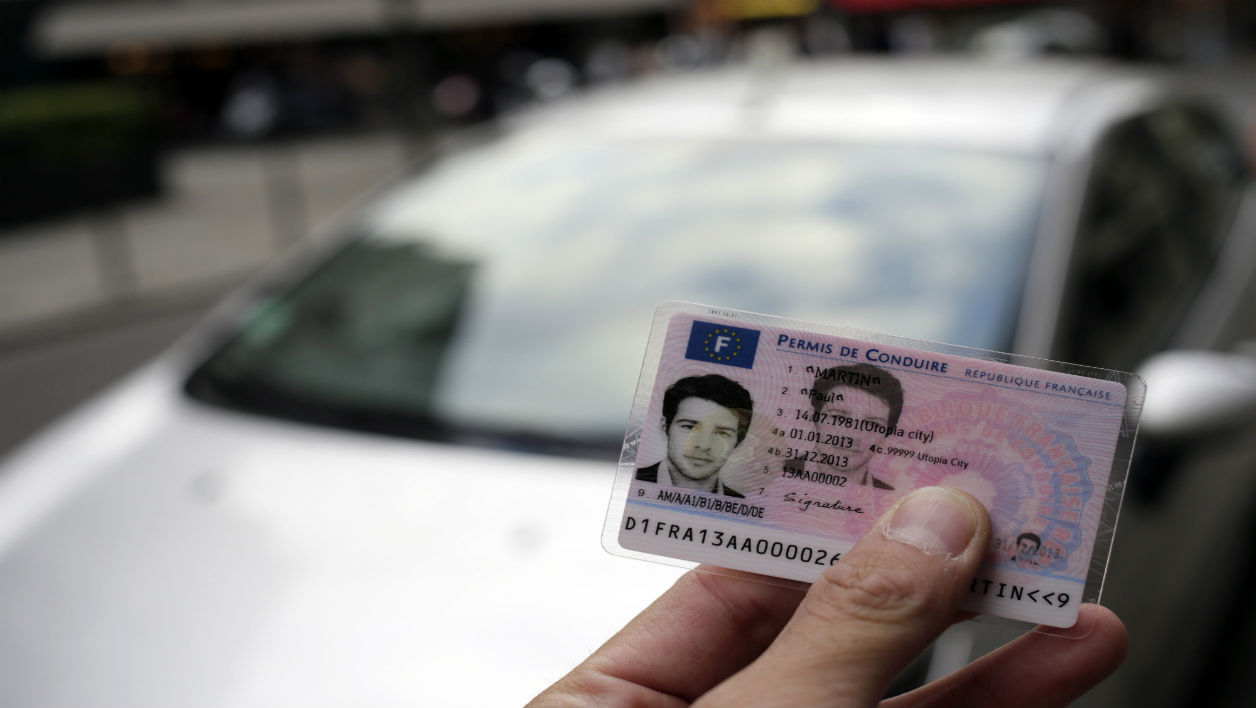 A man holds the first French smart card driver's license in front of a car, on September 11, 2013 in Paris. This secured new driver's license, integrating an electronic chip, will be put into circulation on September 16, 2013. This new license would improve the fight against fraud. AFP PHOTO / KENZO TRIBOUILLARD KENZO TRIBOUILLARD / AFP