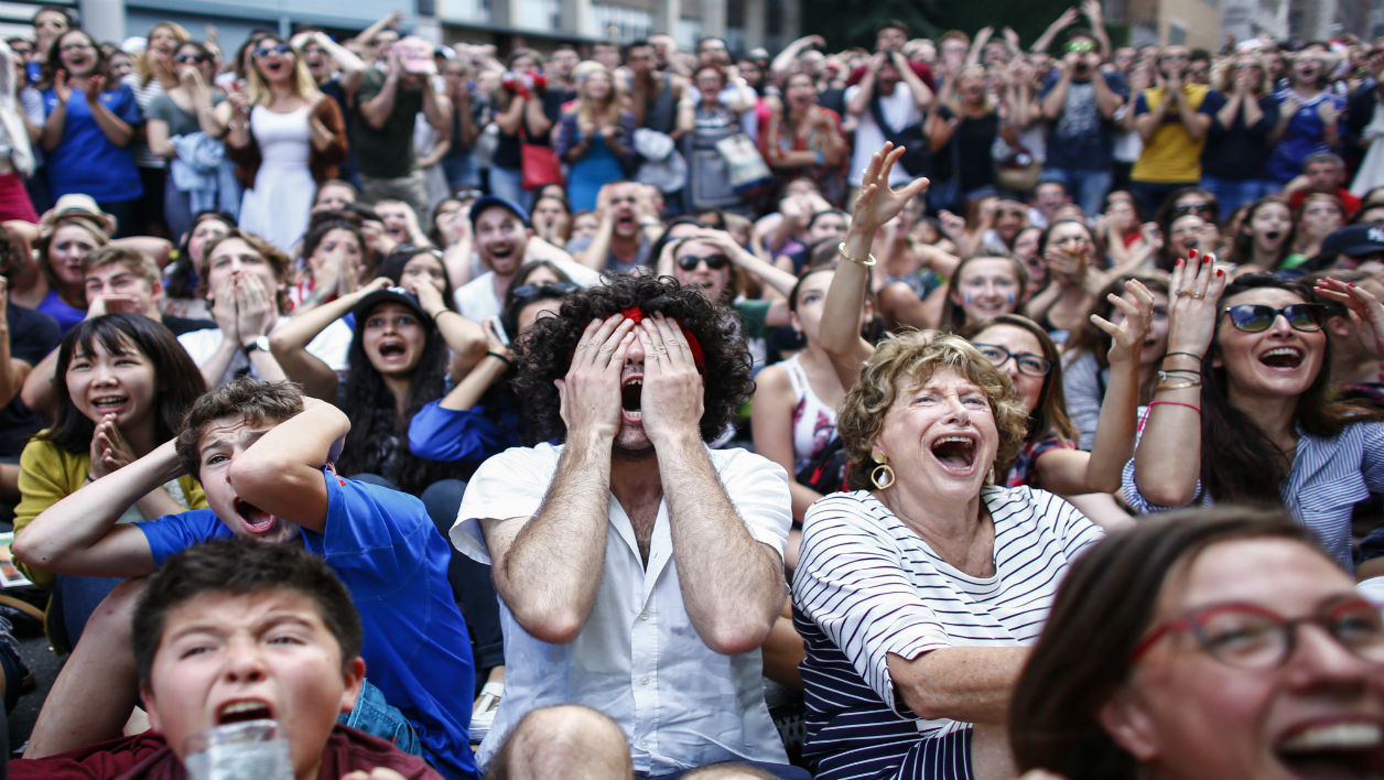 People react as they watch a live screening of the Euro 2016 final football match between France and Portugal, at the Bastille Day Festival in New York on July 10, 2016.