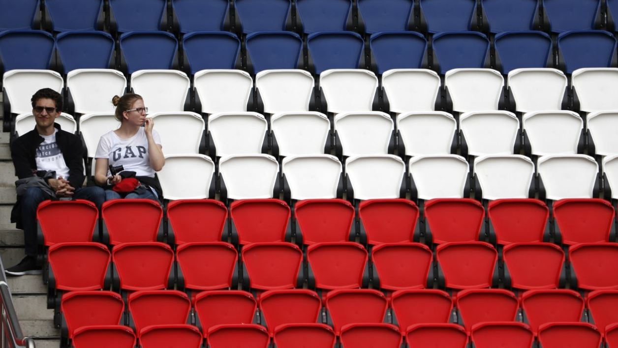 A man and a woman sit in the stands of the Parc des Princes stadium, where seats are painted in the colors of the French flag, prior to the Euro 2016 group C football match between Northern Ireland and Germany at the Parc des Princes stadium in Paris on June 21, 2016.  ODD ANDERSEN / AFP