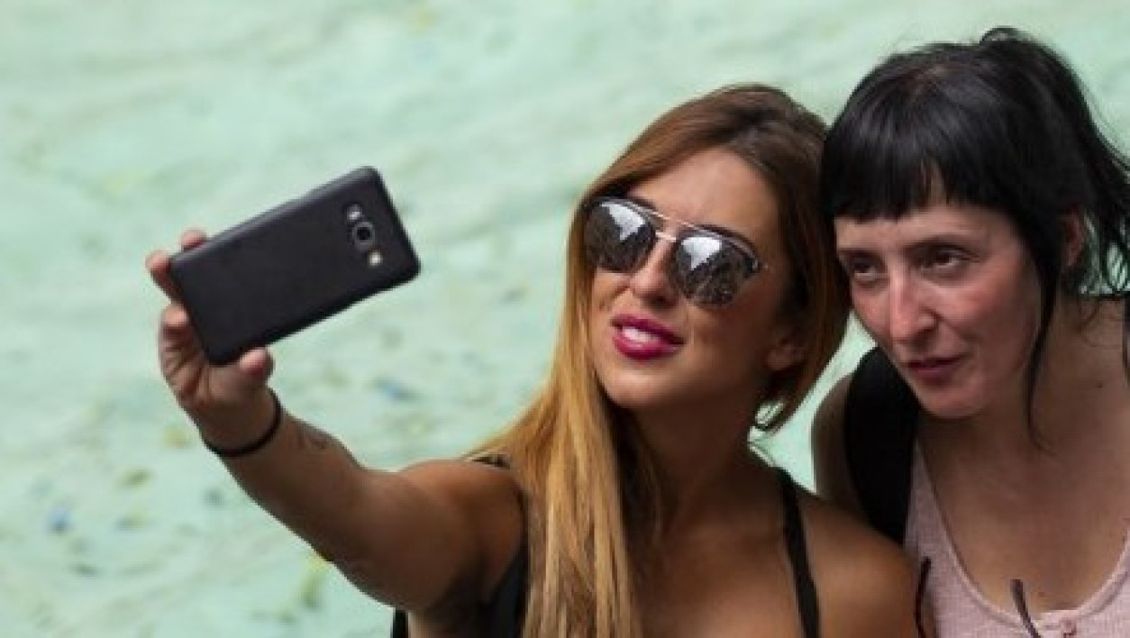 Tourists take a selfie picture with a mobile phone in front of the Trevi Fountain in central Rome on July 14, 2018, as Italy is experiencing its first Summer heat wave with temperatures approaching 40 degrees Celsius.