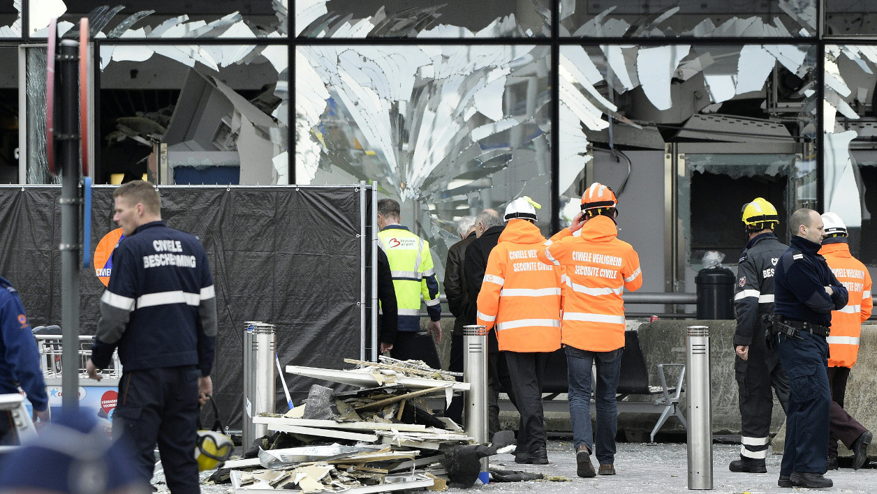 Members of the civil protection walk outside the damaged front of Brussels Airport at Brussels Airport, in Zaventem, on March 23, 2016, a day after triple bomb attacks at the Brussels airport and at a subway train station killed 31 people and wounded more than 200. World leaders united in condemning the carnage in Brussels and vowed to combat terrorism, after Islamic State bombers attacked the symbolic heart of the EU. YORICK JANSEN