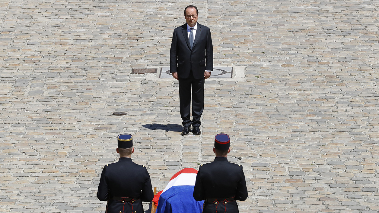 French President Francois Hollande stands in front of the flag-draped coffin of late former French Prime Minister Michel Rocard during a ceremony in his honour at the Hotel des Invalides in Paris on July 7, 2016. PATRICK KOVARIK / AFP