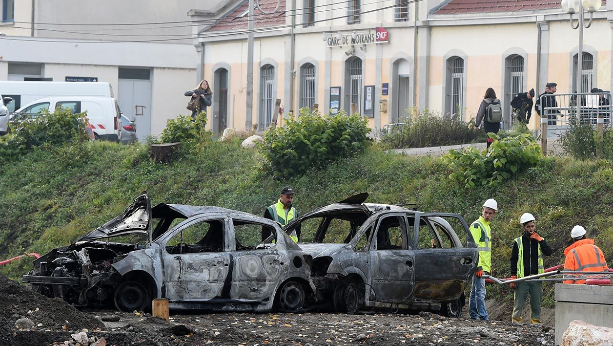 Employees of France's SNCF railway company inspect burnt cars outside the train station of Moirans near Grenoble on October 21, 2015 following violent protests. A traveller community in southeast France launched violent protests while inmates at a jail in the region rioted after authorities refused a request for prison leave, concurring sources said. The local traveller community in the Alpine town of Moirans had requested temporary leave for two jailed members so that they could attend the funeral of someone who had died in an accident last weekend while riding in a stolen car. AFP PHOTO / PHILIPPE DESMAZES